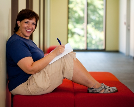 Attractive middle aged smiling woman sitting on a bench writing in her journal room for copy photo