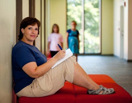Attractive middle aged woman sitting on a bench writing with kids in background Stock Photo