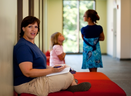 Attractive middle aged woman sitting on a bench with distracting kids part of a series