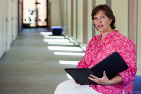 Confident woman sitting in a bright hall getting ready for a meeting Stock Photo