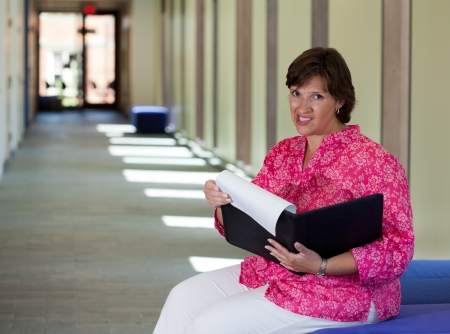 Nervous woman sitting in a bright hall getting ready for a meeting Stock Photo