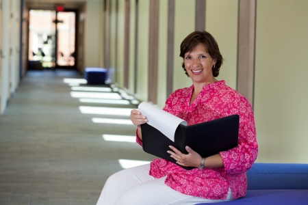 Happy woman sitting in a bright hall getting ready for a meeting Stock Photo