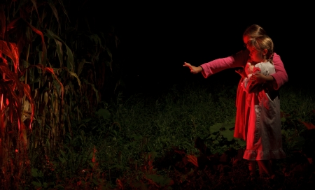 Two girls at the edge of a cornfield at night Stock Photo