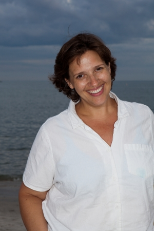 Happy woman in a white shirt on the beach on a cloudy day.