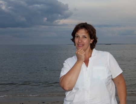 Happy woman in a white shirt on the beach on a cloudy day