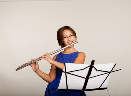 Young girl in a blue dress playing a flute Stock Photo