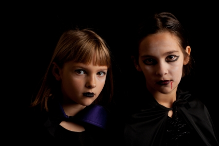 Studio shot of two little girls dresses as vampires looking serious