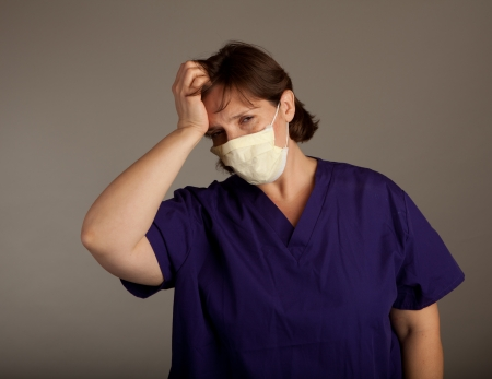 ah1n1: Frustrated Female Doctor or Nurse in mask wearing holding her head