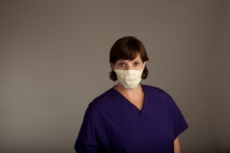 ah1n1: Experienced Female Doctor or Nurse in mask wearing scrubs Stock Photo