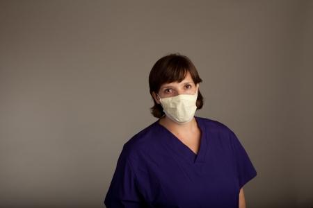 Experienced Female Doctor or Nurse in mask wearing scrubs photo