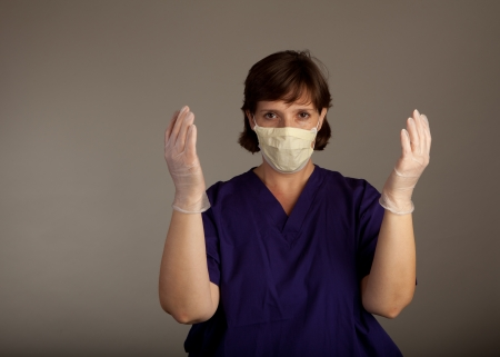 ah1n1: Experienced Female Doctor or Nurse in mask wearing scrubs and gloves