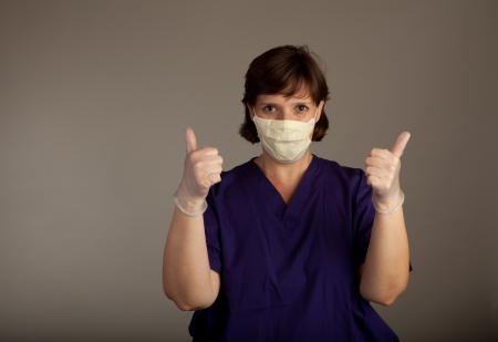 Experienced Female Doctor or Nurse in mask wearing scrubs and gloves giving thumbs up photo