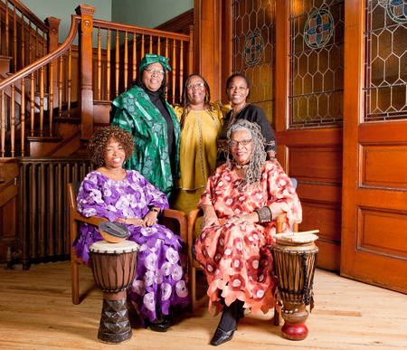 location shot: Location shot of colorfully dressed older African women holding musical instruments smiling and happy