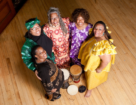 Location shot of colorfully dressed older African women holding musical instruments smiling and happy photo