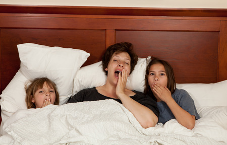 Shots of a mother and her two daughters yawning in bed with white linens part of a series photo