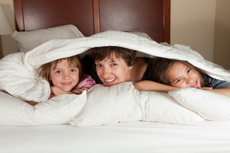 Shots of a mother and her two daughters waking up in bed with white linens part of a series photo
