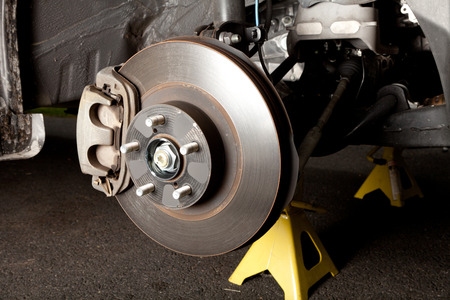Brake disk and caliper assembly on a modern car about to be replaced Stock Photo