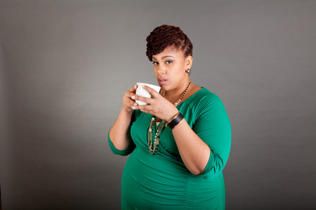 plus sized: Plus sized African american business woman wearing a green dress holding a white ceramic coffee  Stock Photo
