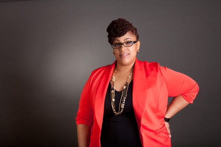 Plus size black woman wearing glasses in a smart business outfit on a neutral grey background