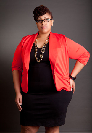 Plus size black woman wearing glasses in a smart business outfit on a neutral grey background photo