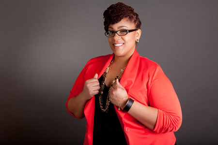 plus size woman: Plus size black woman wearing glasses in a smart business outfit on a neutral grey background