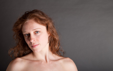 Sexy Female nude redhead with a red drape on a grey background photo