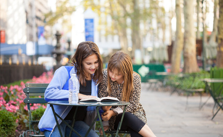Grade  School girls sitting in a city park in new york reading a book with a bottle of water photo