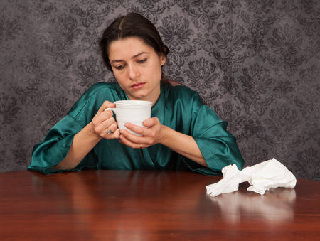 Woman suffering from headache and flu symptoms at home with a coffee cup and tissues