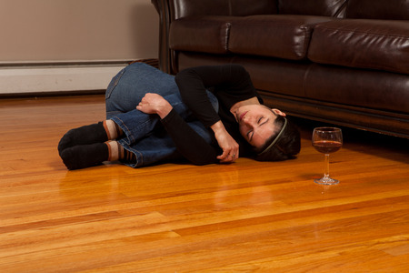 Young woman lying on the floor passed out in the fetal position with a wine glass