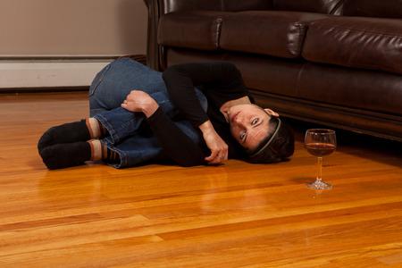 fetal: Giovane donna sdraiata sul pavimento in posizione fetale, con un bicchiere di vino guardando la telecamera
