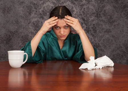 snort: Woman suffering from headache and flu symptoms at home with a coffee cup and tissues
