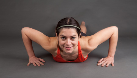 pushup: shot of a fit muscular woman doing a pushup on grey with room for copy Stock Photo