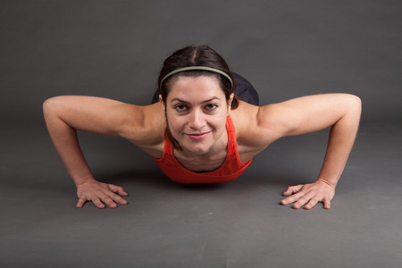 room for copy: shot of a fit muscular woman doing a pushup on grey with room for copy Stock Photo