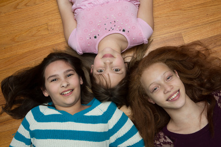 blonde minority: Three young, diverse  girls  lying on a wood floor looking up at the camera. One African American with red hair, one hispanic and one caucasian Stock Photo