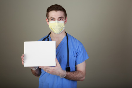 Infection Prevention concept shot of a doctor in mask and gloves holding up a sign with room for your own copy. photo