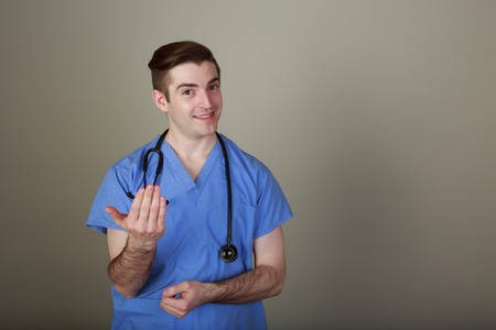 motioning: Funny, friendly young male doctor motioning with his hand to come forward Stock Photo