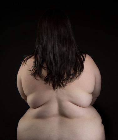 nude young: Плюс размер женщина с длинными темными волосами и бледной кожей, сидя обнаженной на стуле спиной к камере нет открытых частных деталей на черном фоне Фото со стока