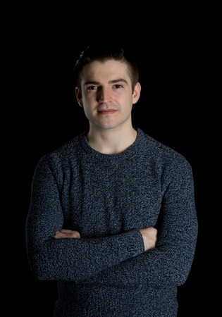 hair studio: Nice low key shot of a young caucasian man with a stylish haircut on a black background in a casual sweater