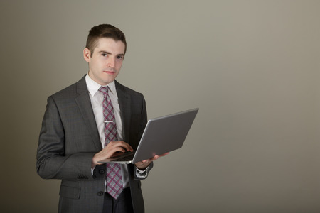 man in suite: Studio shot of a young business man in a suite posing in the studio on a light grey background with a stylish haircut holding a laptop Stock Photo