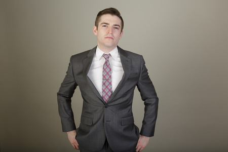 man in suite: Studio shot of a young business man in a suite posing in the studio on a light grey background with a stylish haircut Stock Photo