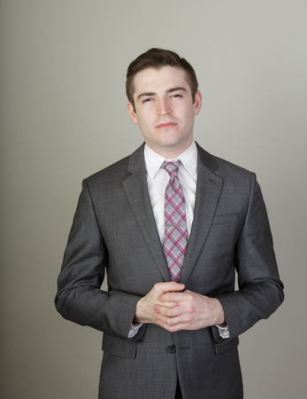 dishonest: Dishonest looking young white male salespersonp in a suite on a grey background