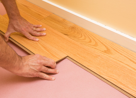 engineered: Series of shots of engineered hardwood floor being installed by a worker over pink felt paper using hand tools Stock Photo