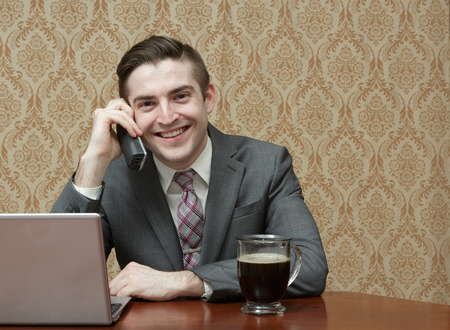 homeoffice: Young business man in a suite and tie with a cup of black coffee on a phone call with a laptop