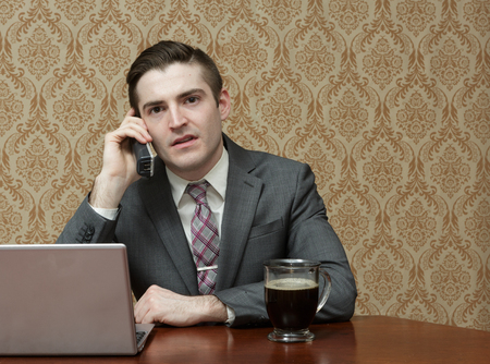man in suite: Young business man in a suite and tie with a cup of black coffee on a phone call with a laptop