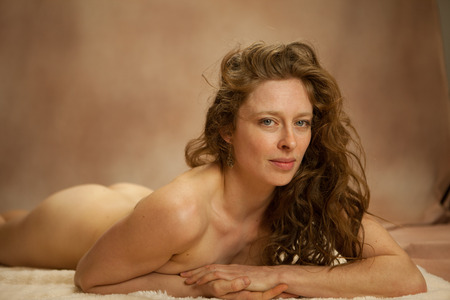 bare breast: A Sepia tone treatment of the classic nude woman. The model is posed on her belly with very shallow depth of field focused on her intense eyes Stock Photo