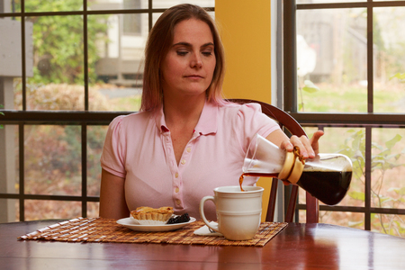 interior shot: Nice interior shot of a woman sitting at the table with a cup of coffee and a breakfast pastry
