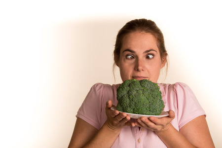 revolting: Woman in a pink shirt on a white background holding a plate of broccoli looking cross eyed