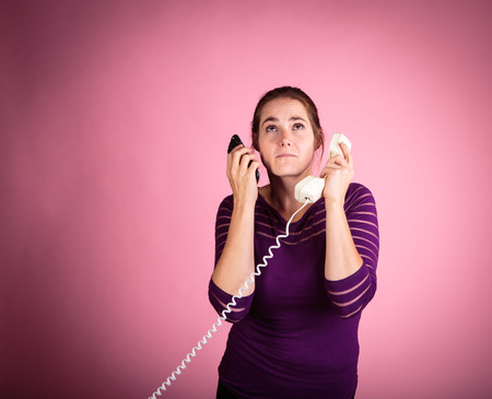 corded: Studio shot of a woman on a pink background with a vintage corded phone having a conversation