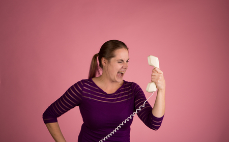 corded: Studio shot of a woman on a pink background with a vintage corded phone having an angry conversation Stock Photo