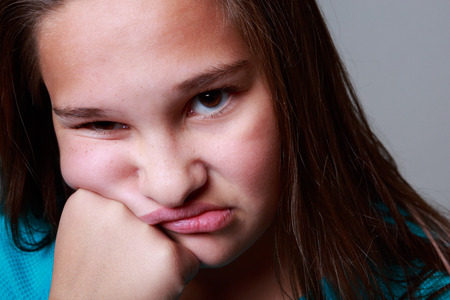 12 year old: Nice studio shots of a a 12 year old girl making faces on a grey background